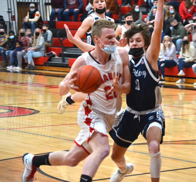 Onaway junior center Jager Mix (left) drives to the basket while Gaylord St. Mary's sophomore Gavin Bebble defends during the first half of a Ski Valley boys basketball matchup in Onaway on Tuesday.