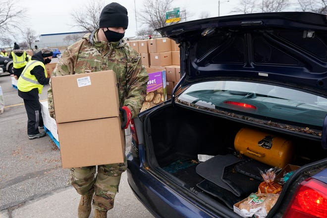 Staff Sgt. Mike Schuster loads two produce boxes into a car at a food bank distribution by the Greater Cleveland Food Bank, Thursday, Jan. 7, 2021, in Cleveland. (AP Photo/Tony Dejak)