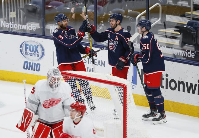 Columbus Blue Jackets defenseman Seth Jones (3) and left wing Eric Robinson (50) celebrate a goal by center Boone Jenner (38) behind Detroit Red Wings goaltender Jonathan Bernier (45) during the second period of the NHL hockey game at Nationwide Arena in Columbus Tuesday, March 2, 2021.