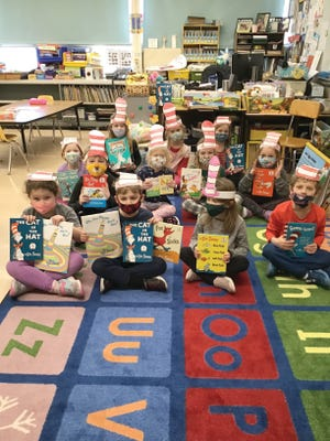 """Students are pictured wearing """"Cat in the Hat"""" style paper hats and holding Dr. Suess books."""