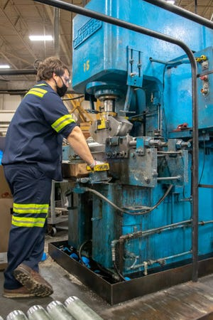 Luke McManaway of Claysville works as a bender at the Picoma plant in Cambridge. Picoma is the country's leading manufacturer of electrical elbows, couplings, and nipples.