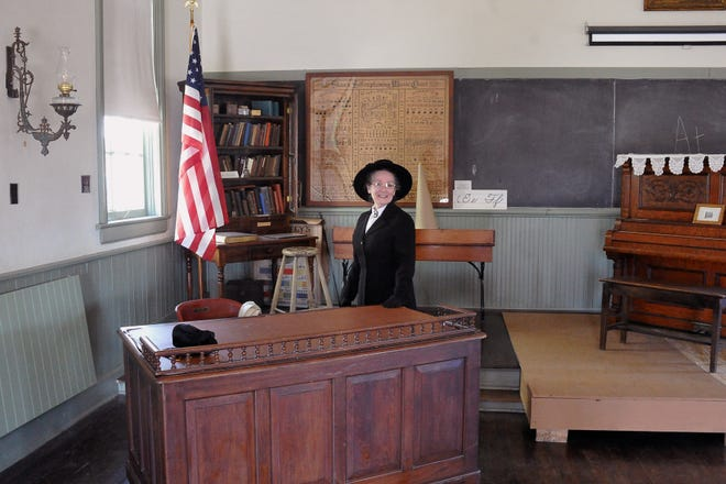 Nell Readon stands at the teachers desk in the old school building on the Wayne County Historical Society campus.