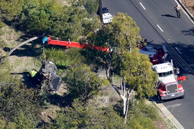 A crane is used to lift a vehicle following a rollover accident involving golfer Tiger Woods, Tuesday, Feb. 23, 2021, in Rancho Palos Verdes, Calif., a suburb of Los Angeles. Woods suffered leg injuries in the one-car accident and was undergoing surgery, authorities and his manager said. [AP Photo/Mark J. Terrill]