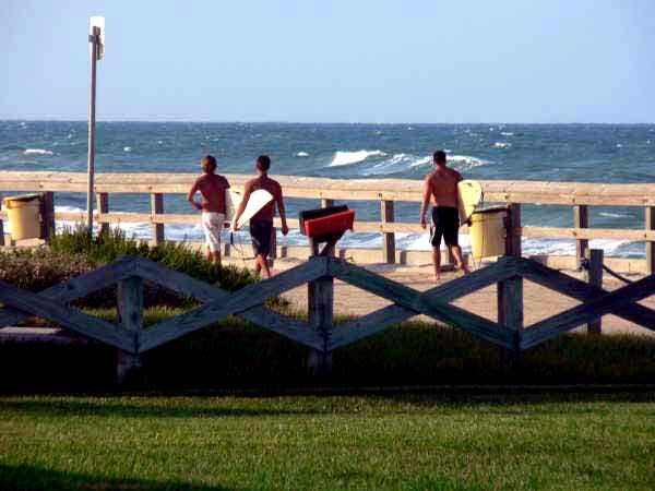 A group of surfers head for the waves at Mary McLeod Bethune Beach Park in Bethune Beach.