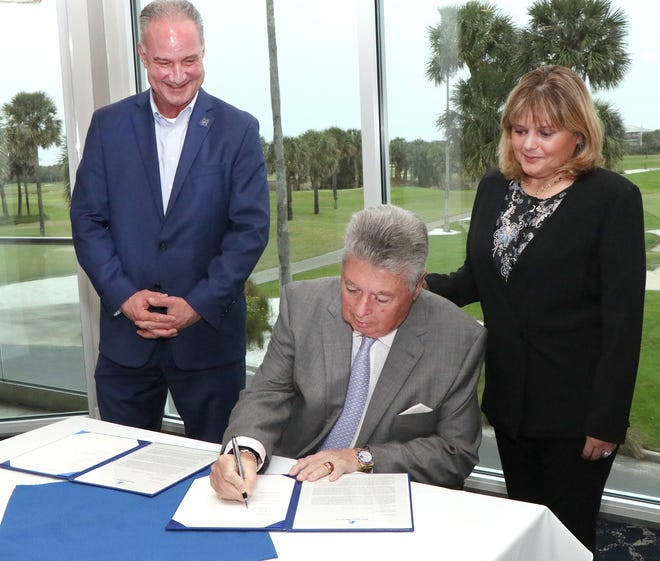 Chuck Grant signs the paperwork as he makes a $4 million dollar donation to Halifax Health Medical Center to support cancer patient services at Oceanside Country Club in Ormond Beach. Looking on is Grant's longtime companion, Miki Nieves Bruinenberg Grant, and Jeff Feasel, Halifax Health president and CEO.