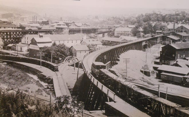 Railroad hub, Carbondale, Pa., on the city's west side. At left is the trestle and passenger station of the New York Ontario & Western. In center is the D&H Coal Company trestle with a train of coal cars. Passing beneath both trestles are the tracks leading to the Jefferson Branch of the New York, Lake Erie & Western Railway, over which the D&H had trackage rights. Van Bergen Foundry buildings may be seen at top left and Maplewood Cemetery at upper right.   The present-day Carbondale Post Office on Dundaff Street is located to the right of where the former O&W passenger station used to stand. / The Pioneer City