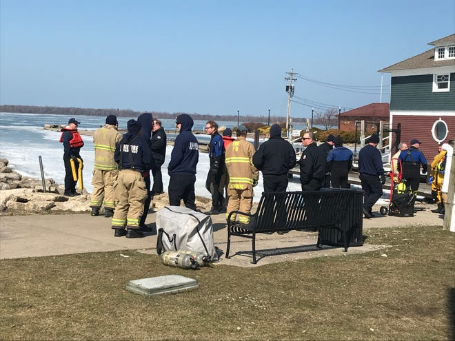 Rescue crews stand near the shoreline at the Chestnut Street Boat Launch in Erie Wednesday afternoon. Authorities responded to a water rescue in which an ice fisherman fell through the ice on Presque Isle Bay. The man was able to get out of the water and walk safely back to shore.