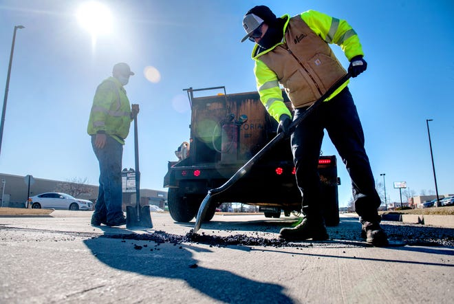 City of Peoria maintenance worker Javier Murillo spreads asphalt into a pothole while fellow worker Matt Savage waits to move on to the next hole Wednesday, March 3, 2021, on North Grand Prairie Drive.