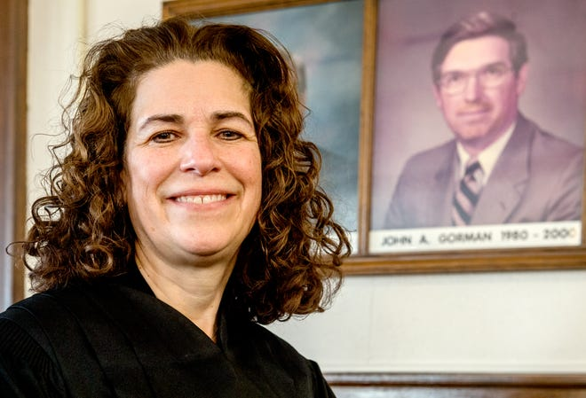 Kate Gorman, chief judge of the 10th Judicial Circuit, poses in front of a portrait of her father, retired U.S. Magistrate John Gorman, at the Tazewell County Courthouse. John Gorman served as the chief judge of the 10th Judicial Circuit from 1994 to 1998.