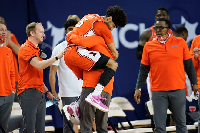 Illinois guard Andre Curbelo (5) jumps into the arms of head coach Brad Underwood in the second half against Michigan in Ann Arbor, Mich., Tuesday, March 2, 2021.