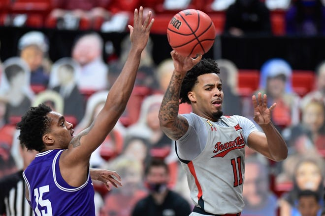 Texas Tech's Kyler Edwards (11) passes the ball during the first half of a Big 12 Conference game Tuesday against TCU at United Supermarkets Arena. Edwards scored 17 of his season-high and game-best 20 points in the first half.