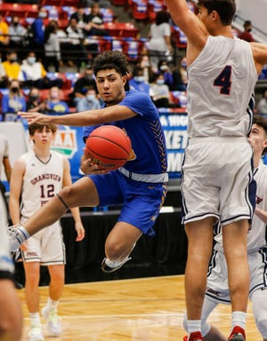 Orlando Christian Prep's Josh Blazquez passes around the back of Grandview Prep's Pedro Brown in the second half of the FSHAA Boys State 2A semifinal on Wednesday at The RP Funding Center in Lakeland.
