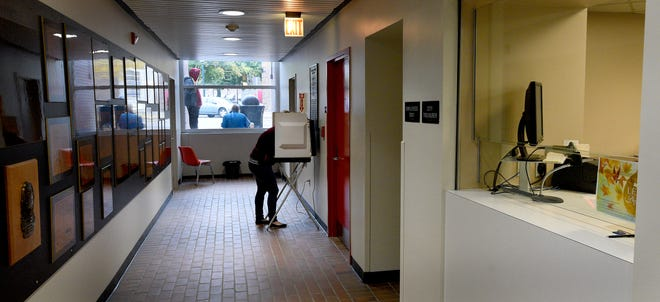 A resident fills out her ballot at Monroe City Hall during the Presidential Election last November. This hallway could soon be cordoned off as part of a series of modifications the city is considering to the first floor of the building.