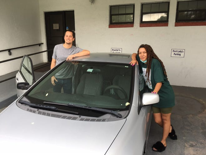 Jack Wharton, left, goes over particulars of the 2009 Honda Civic that Jessica Martinez received on Tuesday at St. Paul AME Church in northwest Ocala. Martinez, a single mom with four children, lost her job due to the pandemic and needs a car to take her 6-month-old child to Gainesville for medical appointments. She was selected to receive the car based upon the positive impact it could have as she tries to improve her situation.