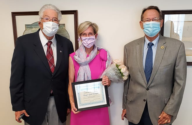 From left, Donald Singer and Skip Aldrich, co-chairs of the Citizens' Association, stand with Mayor Gail Coniglio after presenting her with flowers and a certificate of appreciation. The mayor decided not to seek re-election for a sixth term.