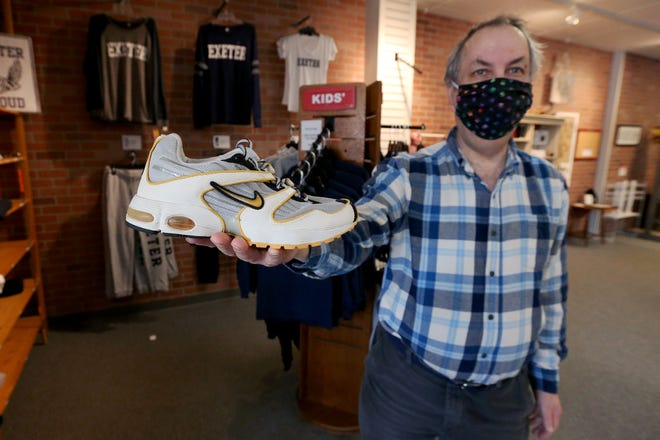 """Bert Freedman, owner of George and Phillips, holds up his pair of Nike """"Air Exeter"""" from 2000. Nike will soon be releasing the """"Exeter Edition"""" running shoes to pay tribute to the town for housing its first American factory."""