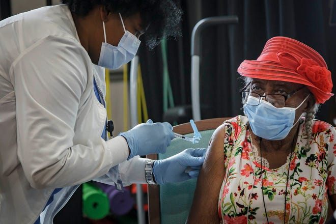 Marie Germain, 94, is inoculated with the first dose of Pfizer COVID-19 vaccine during a vaccination event at Lake Delray Apartments in Delray Beach, Fla., on Wednesday, March 3, 2021.