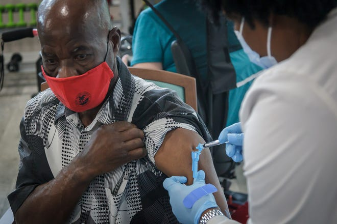 Felix Eloith, 65, is inoculated with the first dose of Pfizer COVID-19 vaccine during a vaccination event at Lake Delray Apartments in Delray Beach, Fla., on Wednesday, March 3, 2021.