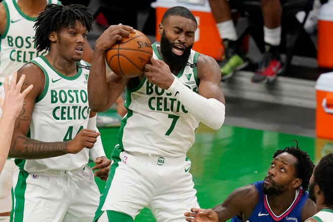 Celtics guard Jaylen Brown snags a rebound against Los Angeles Clippers guard Patrick Beverley, right, during the fourth quarter Tuesday night at TD Garden. Boston center Robert Williams is at left.