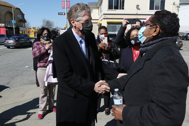 Rhode Island's new governor, Dan McKee, greets the Rev. Israel Mercedes, pastor of Iglesia Vision Evangelica Church on Broad Street in Providence, during McKee's first full day on the job.