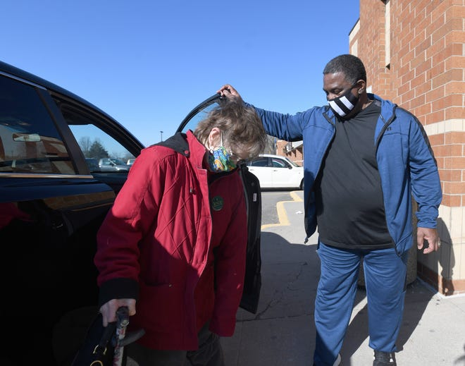 Keith Herring Sr., a volunteer with Faith In Action of Western Stark County, helps Susan Glew, of Massillon, into a local store. Herring is a volunteer driver helping people 65 and older who do not drive get to medical appointments, grocery stores and other errands.
