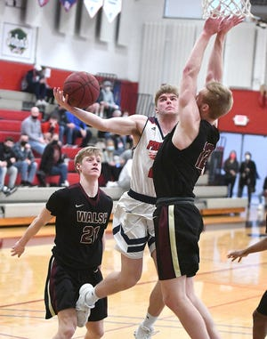 Justin Miller of Malone University splits the defense of Garrison Keeslar, left, and Caleb Canter of Walsh University, Tuesday, March 2 , 2021.