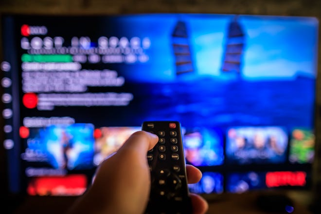 TV remote control in the foreground, Video on demand screen in the blurry background, streaming