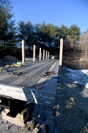 The Stark County Park District worked Wednesday to install a repurposed semitrailer bed across the southern-most section of Petros Lake in Perry Township. The trailer bed is the new footbridge along a walking trail.