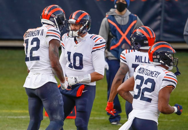 In this Dec. 13, 2020, file photo, Chicago Bears wide receiver Allen Robinson (12) celebrates with quarterback Mitchell Trubisky (10) after scoring a touchdown against the Houston Texans during the first half in Chicago. General manager Ryan Pace had few answers when it came to the two biggest questions facing the Bears in the offseason. He wouldn't rule out anything when it comes to a potential starting quarterback next year, not even a return for Trubisky. And he said the Bears haven't decided whether to use the franchise tag on star receiver Robinson.