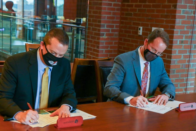 Gardner-Webb University and Cleveland Community College presidents William Downs and Jason Hurst sign agreements for a joint admissions program for nursing students.