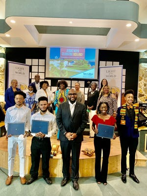 """Front row, left to right: essay writers Dillon Smith (second runner-up), Myles Summerlin (first runner-up), Senior Pastor Kelvin L. Lumpkin, Brianna Witlarge-Isaacs (top essay writer) and program emcee William Moragne. Back row, left to right: Joyce White, Rachel Goldman, Henry """"Hank"""" Battie, Tameka Moore, Kathy Ansley, Phyllis Clay, Beverly Andrews, First Lady Dalia Lumpkin and Darlene Mayes.  Members not pictured: Lem Andrews, Darnell Bacon and Shelli Freeland-Eddie."""