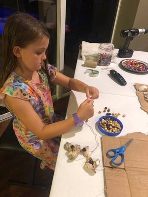 Autumn Courter, 8, assembles shells and embellishments for one of her wind chimes.
