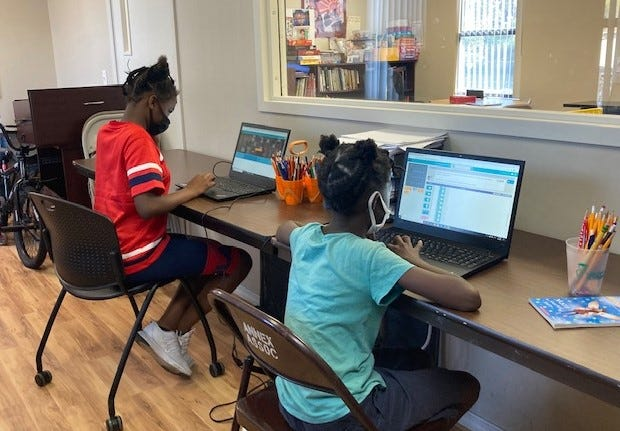 Two students engage in remote learning at Sarasota Housing Authority's LearningCenter. The center is mainlyforstudents, but it also helps parents and other residentswith all kinds of important tasks, from applying forEBTassistance to staying in touch with their children's schools to accessingfinancial literacy courses.