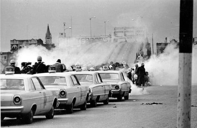 """Tear gas fumes fill the air as state troopers, ordered by Gov. George Wallace, break up a demonstration march in Selma, Alabama, on what is known as """"Bloody Sunday"""" on March 7, 1965. As several hundred marchers crossed the Edmund Pettus Bridge to begin their protest march to Montgomery, state troopers violently assaulted the crowd with clubs and whips. A shocked nation watched the police brutality on television and demanded that Washington intervene and protect voter registration rights for Black Americans."""