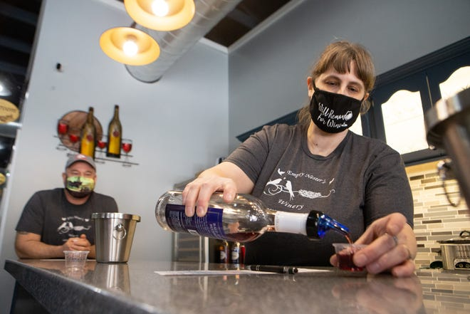"Vickie Clark, right, co-owner of Empty Nester's Winery, pours a sample of their ""Bald Eagle Blueberry"" wine, with her husband Troy Clark looking on. The winery, located at 338 Elmore St. in Lecompton, is the town's sole winery, serving a selection of house-made fruit wines."