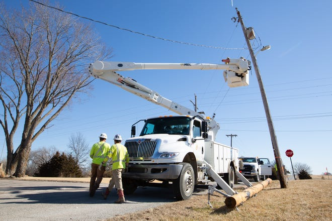 Linemen for Capital Electric Line Builders work to replace electric poles across 74th Street and Silver Road in north Shawnee County Wednesday morning. Utilities have seen their costs soar after bitter cold temperatures in mid-February.