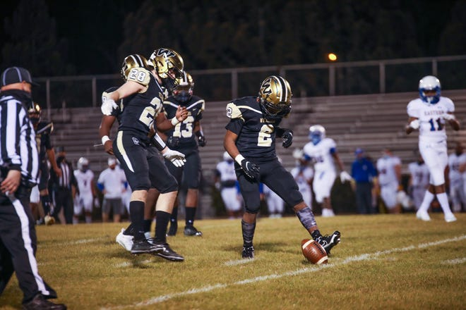 Williams High School's Xavion Jones, right, and Grayson Loy, left, chase down a Bulldogs punt against Eastern Guilford in a game last Thursday.