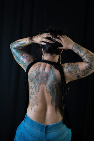 Brandi Halvorson displays her arm and back tattoos for Inked Magazine's cover model contest. Halvorson is a retired Pueblo police officer, who has found new meaning in her life through her tattoo art, and activism within the indigenous community.