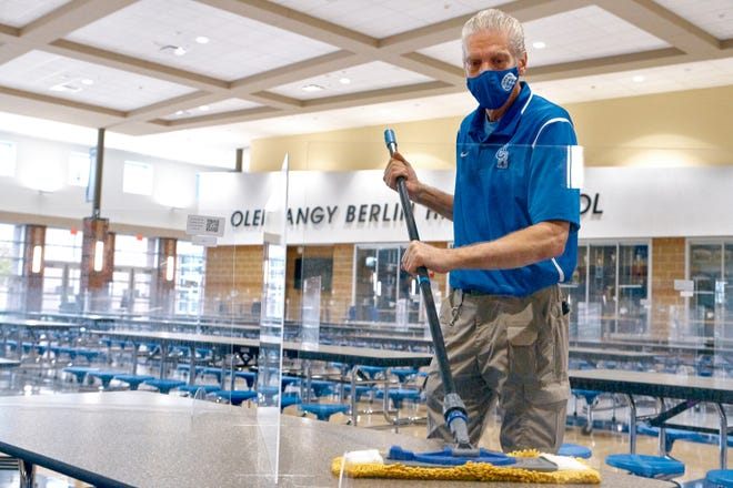 Custodian Ed Strayer cleans lunch tables at Olentangy Berlin High School recently. Olentangy Schools is expected to return to a full-time, in-person learning model March 15.