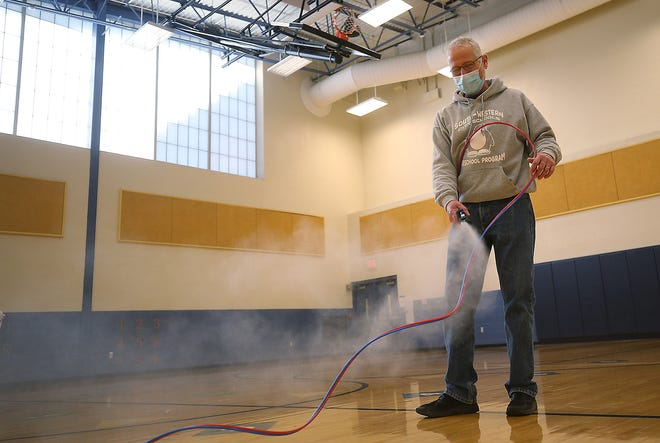 Joe Conley, head custodian at the South-Western City School District's Bolton Crossing Elementary School, uses a mister to disinfect the gym March 3. The custodial staff clean and disinfect the school daily, including cleaning every door handle twice a day. On Wednesdays, when students are not in the building, staff do a deep cleaning.
