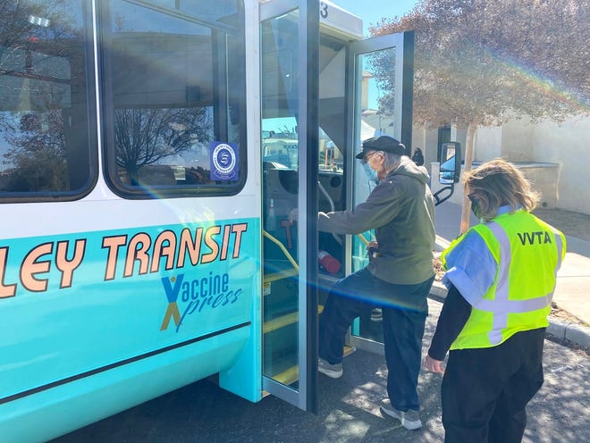 Victor Valley Transit Authority bus operator Brandi Neill waits as passenger Ralph Duran boards the Vaccine Xpress bus after being inoculated at the Our Lady of the Desert Church in Apple Valley.