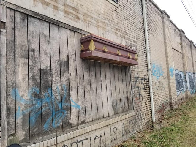 National Casket Company had a production facility on Riverside Drive in the early part of the 20th Century, and this half-casket over a former loading dock is probably a remnant of that business.