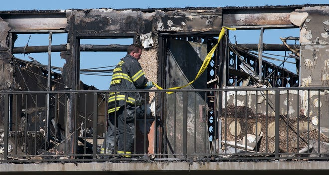 An official works the scene after a predawn four-alarm fire tore through the Howard Johnson hotel in Gloucester Township on Wednesday, March 3, 2021.