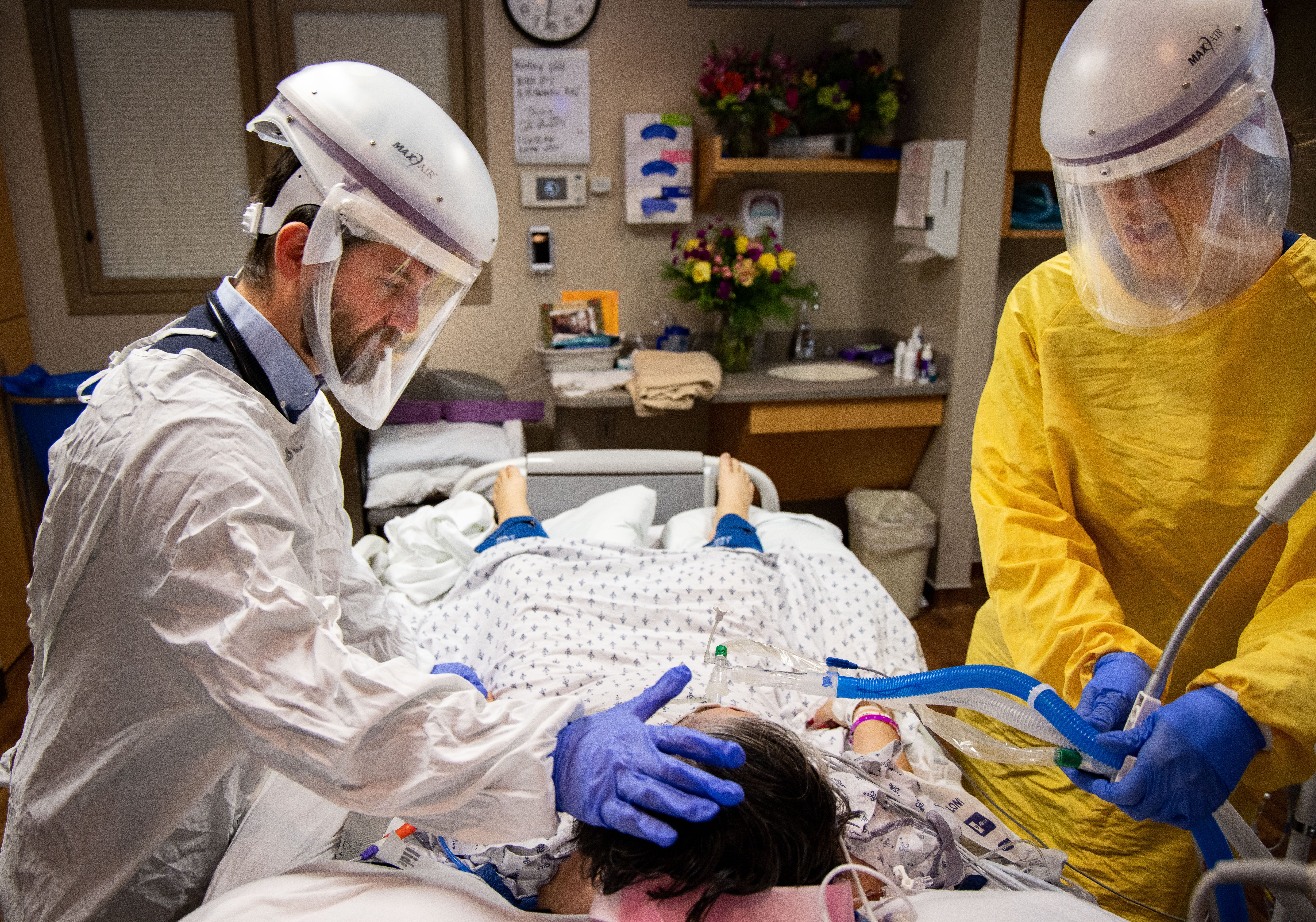 Infectious disease specialist Dr. Dan Fulton, left, checks on a COVID-19 patient in the ICU at Mary Greeley Medical Center in Ames on Dec. 16, 2020.