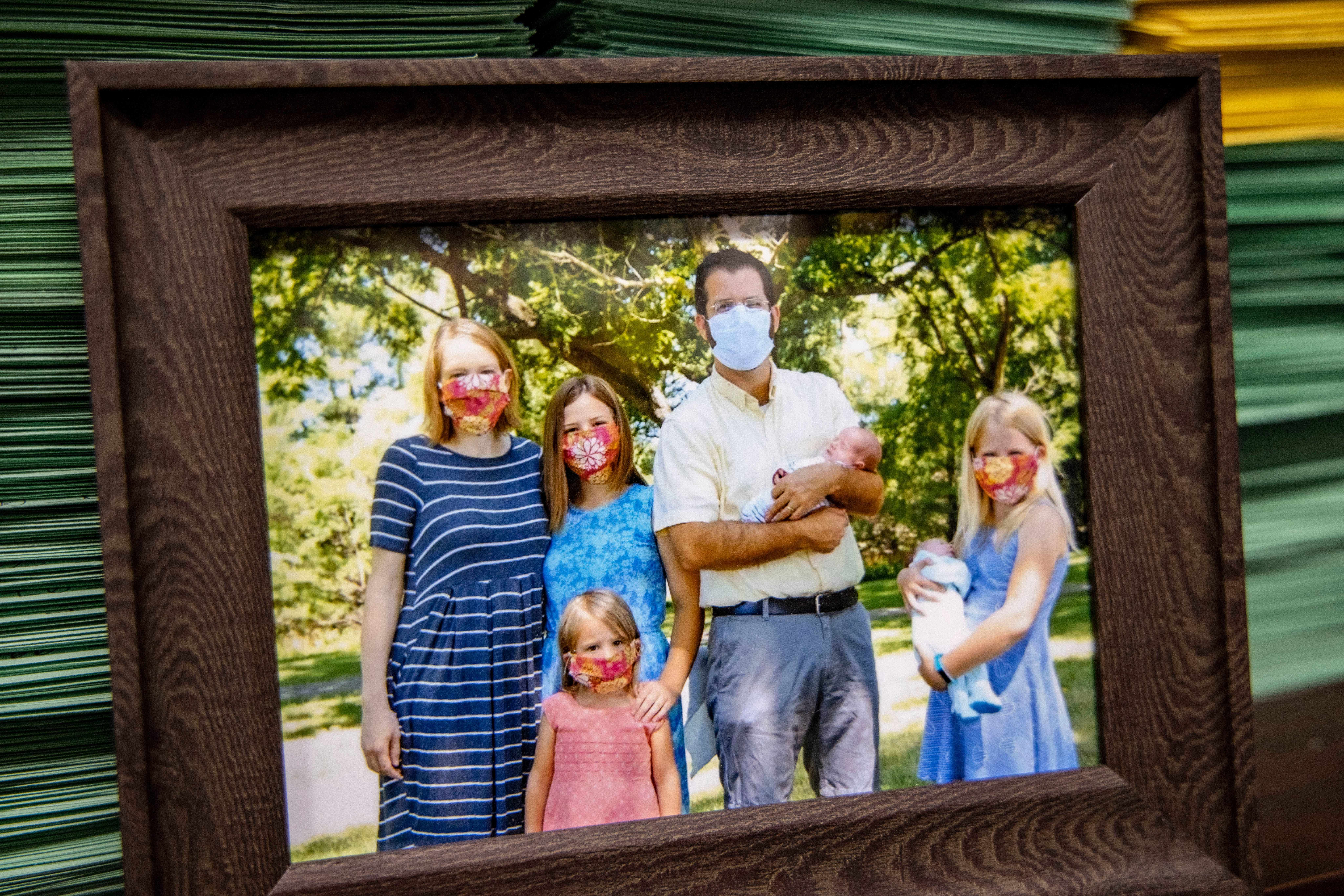 A family photo from 2020 sits in front of patient cards in Dr. Fulton's office. He's the father of five daughters, including twins born during the pandemic.