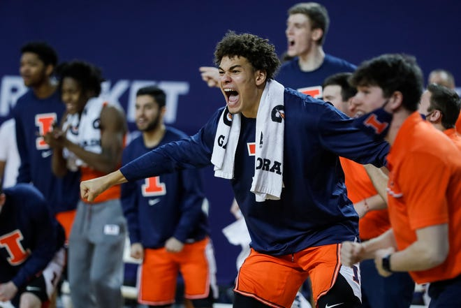 Illinois players celebrate an out of bounds call that gives possession back to Illinois during the first half against Michigan at the Crisler Center in Ann Arbor, Tuesday, March 2, 2021.