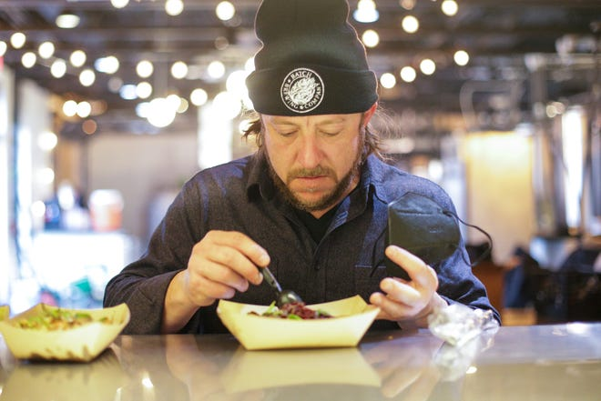 Stephen Roginson, Owner and Founder of Batch Brewing Co, samples dishes from a pop-up kitchen with Chef Kate Williams of Lady of the House at the Detroit brewery on Feb. 24, 2021, in Detroit. In light of the pandemic, Roginson offers local chefs a venue to sell their food to brewery patrons. He also steps in to help wherever he can.
