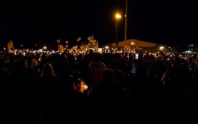 Family, friends and fellow students held up their candles during a candlelight vigil for Madelynn Troutt in the parking lot of Butler High School in Shively, Ky. March 2, 2021