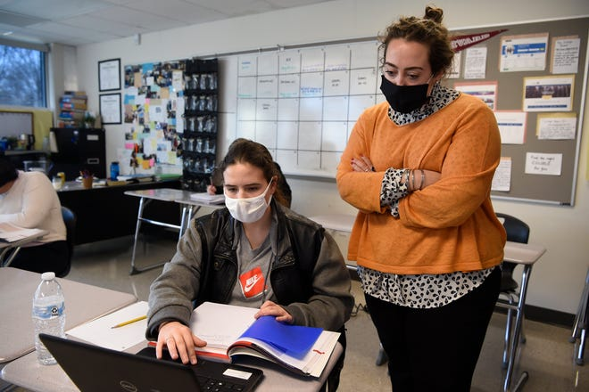 Global Perspective teacher, Meredith McGinnis helps junior Jada Blake with an assignment in class at John Overton High School in Nashville, Tenn., Wednesday, March 3, 2021.