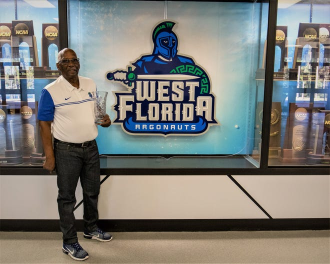 Ewell Howard, 82, poses in front of a UWF logo in an undated photo. Howard has held a variety of roles with the university in a career spanning over five decades.
